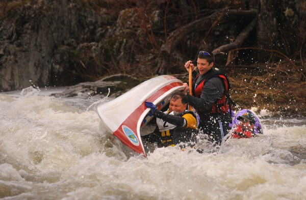 David Slagger (front) and his crew mates Gage Needham and Linus Lewis get ejected from their boat as it hits a rock at Six Mile Falls rapid during the 2013 Kenduskeag Stream Canoe Race.