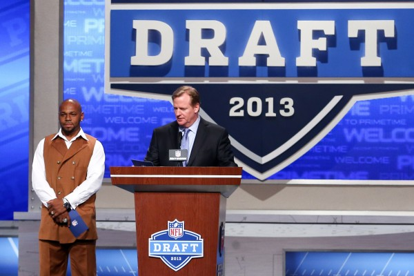 Former New England Patriot Kevin Faulk (left) announces the 52nd overall pick to the New England Patriots with NFL commissioner Roger Goodell (right) during the 2013 NFL Draft Friday night in New York