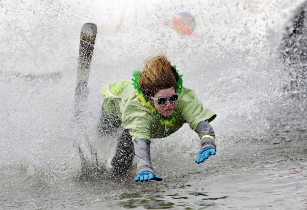 Kelsey Myers, of Freeport, goes headfirst into the pond, Sunday, April 7, 2013, at the Sunday River Ski Resort in Newry, Maine.