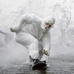 Tony Ricciardi, of Yarmouth, Maine, dressed as a Yeti, skims successfully across the pond to win the annual pond skimming competition, Sunday, April 7, 2013, at the Sunday River Ski Resort in Newry, Maine.