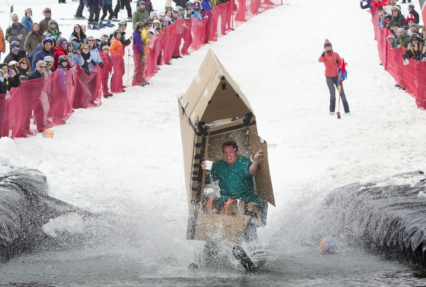 Rob Tragemann of Newry, sunk while trying to skim across the pond inside a cardboard outhouse Sunday, April 7, 2013, at the Sunday River Ski Resort in Newry, Maine.