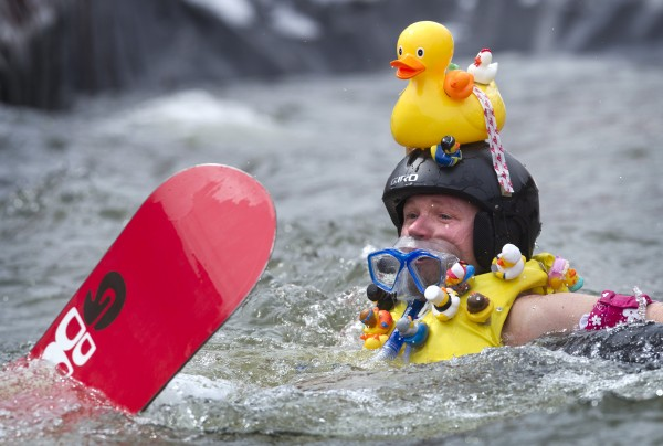 Conrad Armstrong of Boston wore a rubber ducky-themed contest in his unsuccessful attempt to skim across a pond on a snowboard, Sunday, April 7, 2013, at the Sunday River Ski Resort in Newry, Maine.