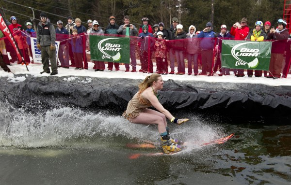 A skier in a Pocahontas costume skims across the water Sunday, April 7, 2013, at the Sunday River Ski Resort in Newry, Maine.