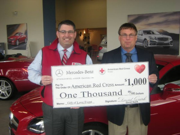 Todd Nadeau (left), chapter executive for the Pine Tree Chapter of the American Red Cross, accepts a donation from David Quirk, vice president of Quirk Auto Group.