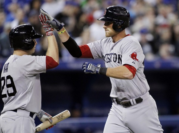 Boston's Will Middlebrooks (right) high fives Daniel Nava after hitting his third home run of the game against the Toronto Blue Jays Sunday in the seventh inning at the Rogers Centre in Toronto.