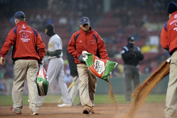 Members of the Fenway Park grounds crew prepare the infield during the second inning in a game between the Boston Red Sox and the Oakland Athletics at Fenway Park Tuesday night. Oakland won the rain-shortened game 13-0 after seven innings.
