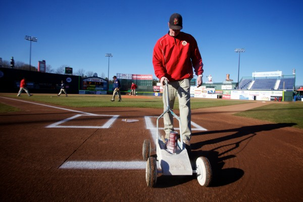 Portland Sea Dogs groundskeeper Tim Miller paints the batters box on opening day at Hadlock Filed in Portland Thursday.