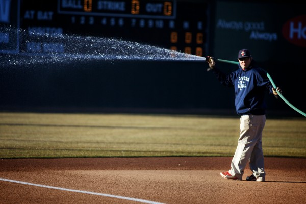 Assistant Head Groundskeeper Jason Cooke wets the infield Thursday on opening day at Hadlock Field.