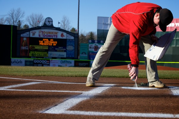 Portland Sea Dogs groundskeeper Tim Miller paints home plate on opening day at Hadlock Field in Portland Thursday in Portland.
