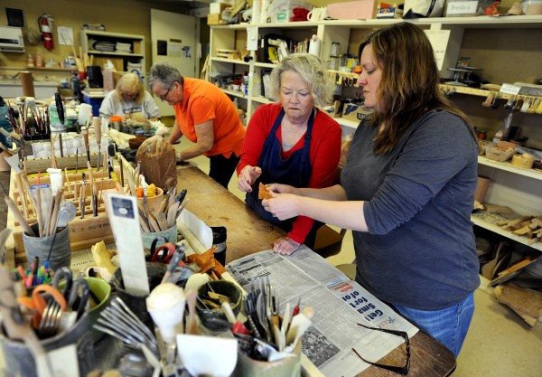 Lori Heagle (right), a volunteer at the Hammond Street Senior Center, helps Lynda Flower with a piece she is working on in sculpture class. Heagle teaches three classes a week at the center.