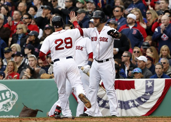 Boston Red Sox first baseman Mike Napoli (12) greets Boston Red Sox left fielder Daniel Nava (29) as he scores against the Tampa Bay Rays during the third inning at Fenway Park on Monday.