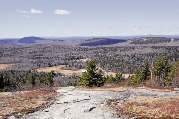 From the access trail that ascends Bald Mountain in Dedham, the view to the southwest encompasses nearby Great Pond Mountain in Orland (left), the Camden Hills on the distant horizon (center). and Dodge Hill (right).