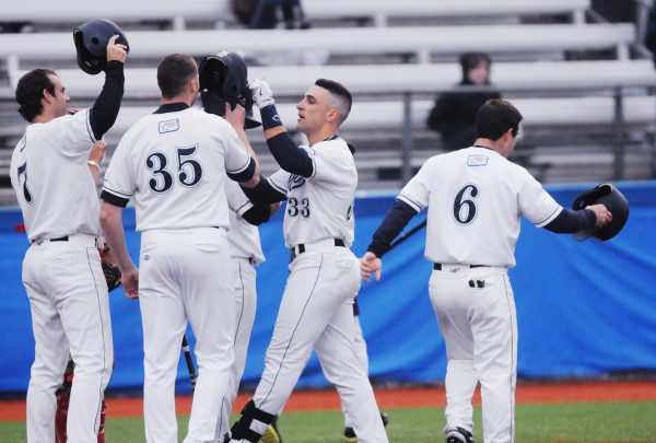 UMaine outfielder Kyle Silva (33) accepts a salute from his teammates, Nick Bernardo (7) Fran Whitten (35), and Eric White (6) after driving them home on his grand slam against Thomas College during fourth inning action on Tuesday at Orono.
