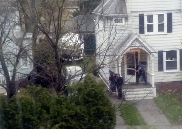 In this neighbor's view from across the street, law enforcement agents look around the corner of a house where Boston Marathon bombing suspect Dzhokhar Tsarnaev was believed to be hiding in Watertown, Massachusetts, April 19, 2013.
