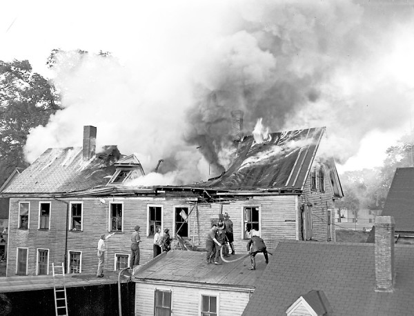 An explosive fire of undetermined origin swept through the Viner Shoe company warehouse on Newbury street in Bangor. on Tuesday evening, July 3, 1951 and caused about $30,000 damage. Bangor firemen are shown as they attacked the flames from nearby smaller buildings. The blaze was confined to the one structure.