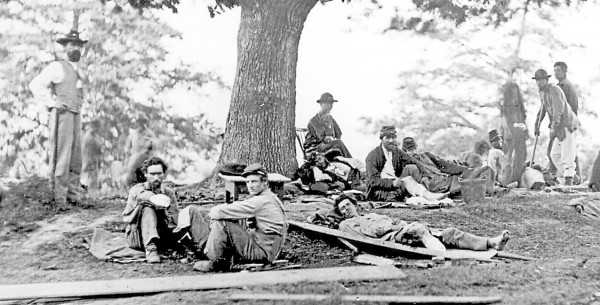Union soldiers wounded during the Battle of Chancellorsville in Virginia rest outside a field hospital near Fredericksburg on Saturday, May 2, 1863. The bearded soldier sitting at left has lost his right arm below the elbow; a surgeon amputated the right foot of the young soldier lying on the stretcher.
