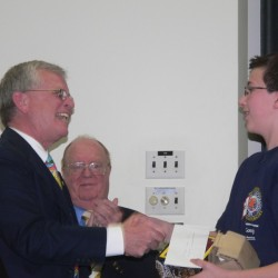 Winner Archer Thomas of Buxton, receiving his award from Brian Cushing, Bee Coordinator and Matthew Ward, Final Round Moderator