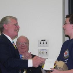 Winner Archer Thomas of Buxton, receiving his award from Brian Cushing, Bee Coordinator and Matthew Ward, Final Round Moderator