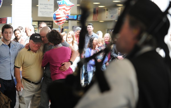 Marine Cpl. Jacob Campbell of China is hugged by his father, John, mother, Elizabeth, and brother Cameron at the Bangor International Airport on Sunday as the Rocky Bay Pipe Band plays bagpipes to welcome the soldier home after a tour of Afghanistan. Campbell was once a member of the band.