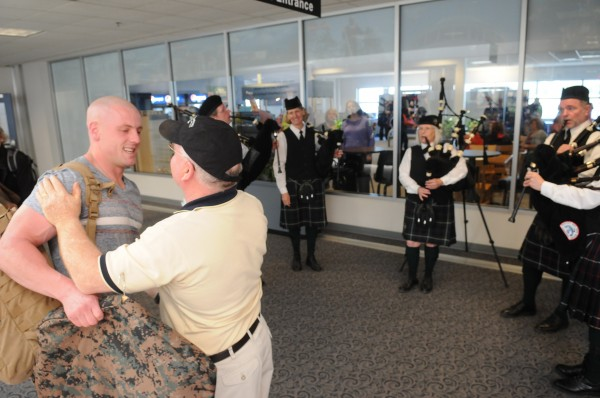 Marine Cpl. Jacob Campbell of China is hugged by his father, John, at the Bangor International Airport on Sunday as the Rocky Bay Pipe Band plays bagpipes to welcome the soldier home after a tour of Afghanistan. Campbell was once a member of the band.