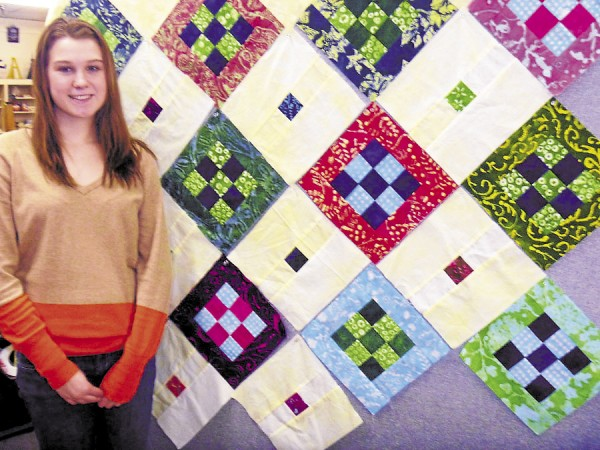 Morgan Williams of Bangor, a senior at Bangor High School, has pinned pieces of her quilt to a design board in order to organize them in preparation for sewing. She is a student in the fabric design class taught by Kathleen Hartley.