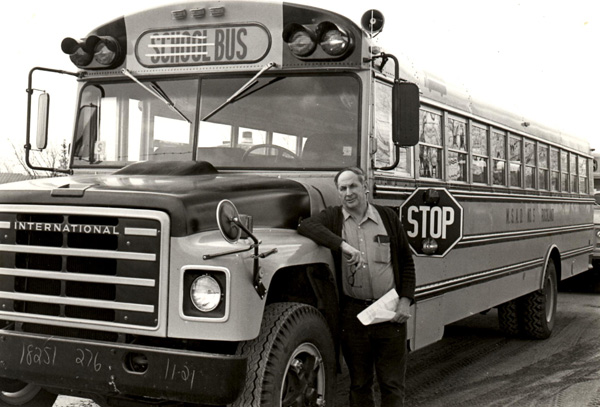 Bud Wood rests against one of the SAD 5 buses in Rockland. Wood drove school buses for 50 years.