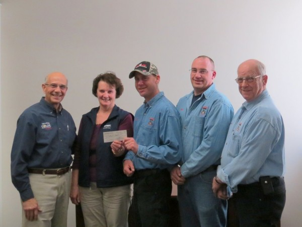 "Rich Pfirman, Barb Whitney awarding a $10,000 check from the Plummer Foundation to the Dexter Fire Dept, represented by Chief Matt Connor, Asst. Chief Rick Stocker, and Lt. Everett Hibbard on 4/26/2013 for a new ""Jaws of life"" tool"