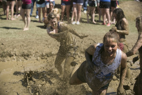 Two University of Maine students splash mud on each other during a game of oozeball during Maine Day celebrations on Wednesday, May 1, 2013. Although the game is played like volleyball, oozeball has no scoring, no formal rules and no winner.