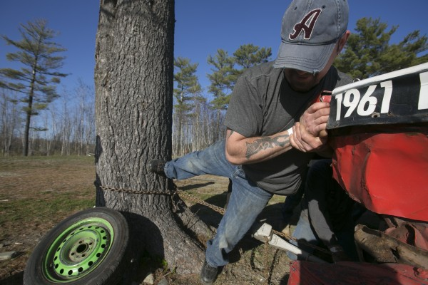 A friend tries to help correct a bent frame on Andrew and Brett Crosby's race car at Speedway 95 in Bangor on Saturday, May 4, 2013. The frame was bent during a collision in the previous race. Brett and his son Andrew are from Hermon and have been racing since 2000.