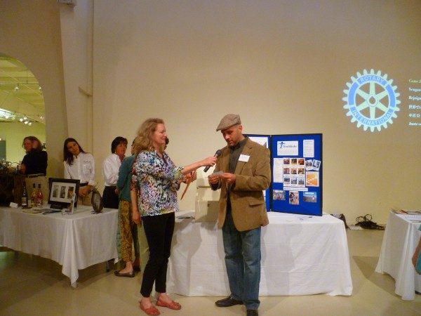 """Drawing the Winning Ticket&quot - Seth Walton, AmeriCorps Vista Community Programs Director of Youthlinks, announces the raffle winner at the Business After Hours at the Owls Head Transportation Museum.  Standing beside him is Robin McIntosh, Membership Services Manager of the Penobscot Bay Regional Chamber of Commerce."