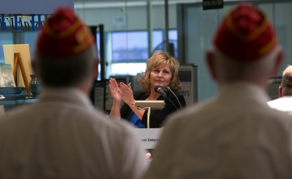 Maine's first lady Ann LePage applauds veterans during a speech at the 10th anniversary celebration of the Maine Troop Greeters on Armed Forces Day at Bangor International Airport on Saturday, May 18, 2013.