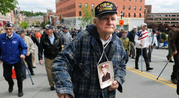 Korean War veteran Bernard Eaton of Amhurst holds a picture of his brother Kyle Eaton while marching in the Memorial Day parade in Bangor. The two brothers sevrved in the Navy during the Korean War, but Kyle Eaton, a pilot, was lost during a mission. &quotHe is still there as far as I know,&quot Bernard said.
