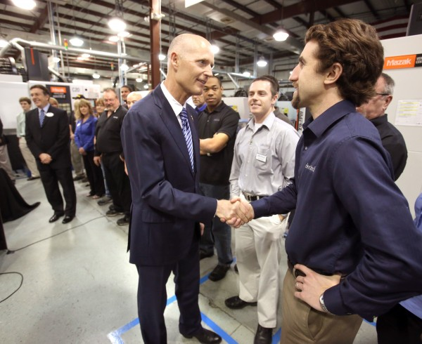 Gov. Rick Scott, left, greets Sal Gerace, a product development manager at .decimal, Inc., during a visit to the medical device manufacturer's facility in Sanford, April 29, 2013.