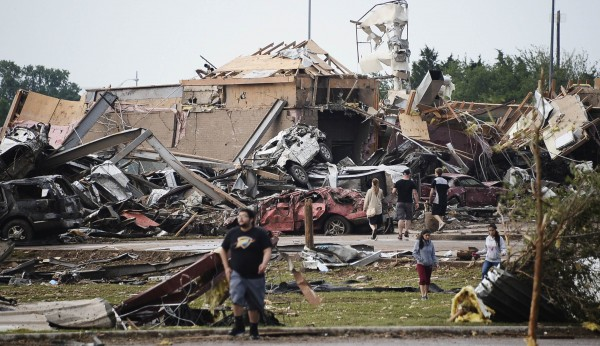 People walk near destroyed buildings and vehicles after a tornado struck Moore, Okla., near Oklahoma City, May 20, 2013. A 2 mile wide tornado tore through the Oklahoma City suburb of Moore, trapping victims beneath the rubble as one elementary school took a direct hit and another was destroyed.