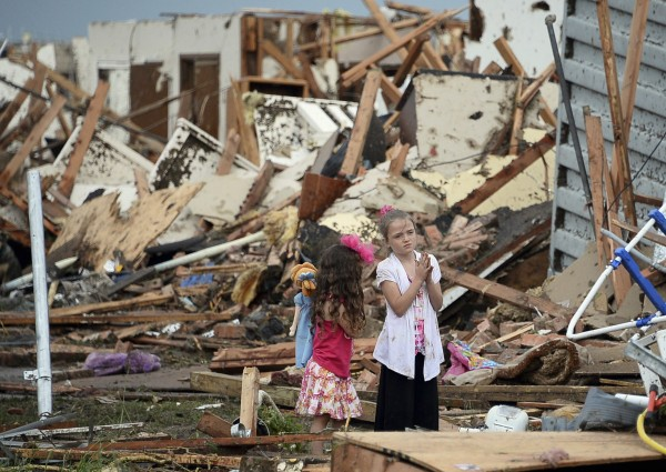 Two girls stand in rubble after a tornado struck Moore, Okla., May 20, 2013. A 2-mile-wide tornado tore through the Oklahoma City suburb of Moore on Monday, killing at least 24 people while destroying entire tracts of homes, piling cars atop one another, and trapping two dozen school children beneath rubble.