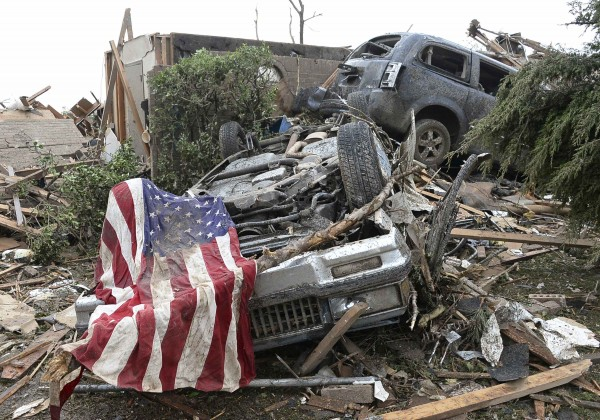 An American flag lies on top of an overturned car after a tornado struck Moore, Okla., May 20, 2013. A 2-mile-wide tornado tore through the Oklahoma City suburb of Moore on Monday, killing at least 24 people while destroying entire tracts of homes, piling cars atop one another, and trapping two dozen school children beneath rubble.
