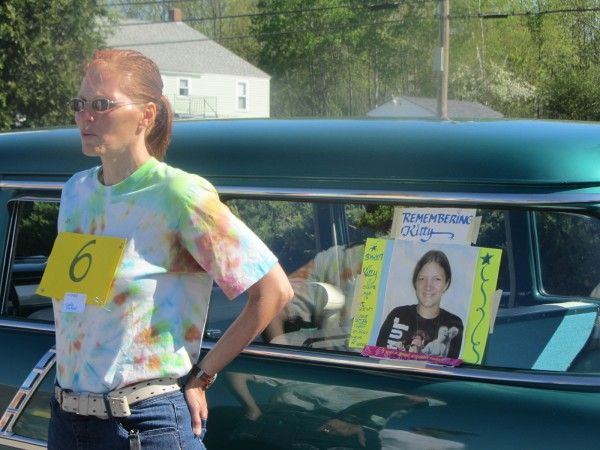 Cindy Packard of Winslow stands next to a car carrying family members of Kitty McGuire as well as a poster of the 13-year-old Troy girl who committed suicide in March.