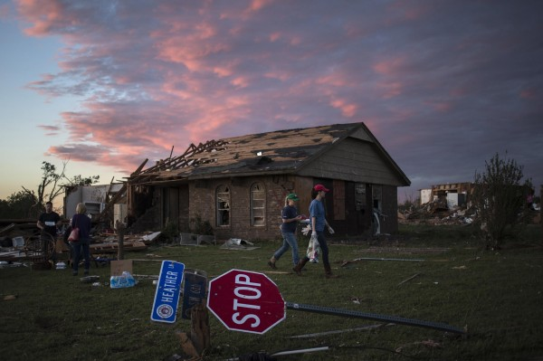 Volunteers walk past a downed street sign after handing out food to home owners sitting in front of their house left devastated by a tornado, in Moore, Okla., on Tuesday. Rescuers went building to building in search of victims and survivors picked through the rubble of their shattered homes on Tuesday, a day after a massive tornado tore through the Oklahoma City suburb of Moore, wiping out blocks of houses and killing at least 24 people.