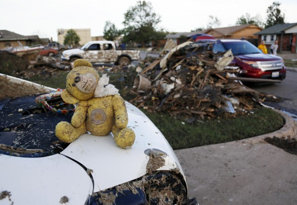 A teddy bear salvaged from the rubble of a tornado-destroyed home sits on the boot of a vehicle, in Moore, Okla., on Tuesday. Rescuers went building to building in search of victims and thousands of survivors were homeless after a massive tornado tore through the Oklahoma City suburb of Moore.