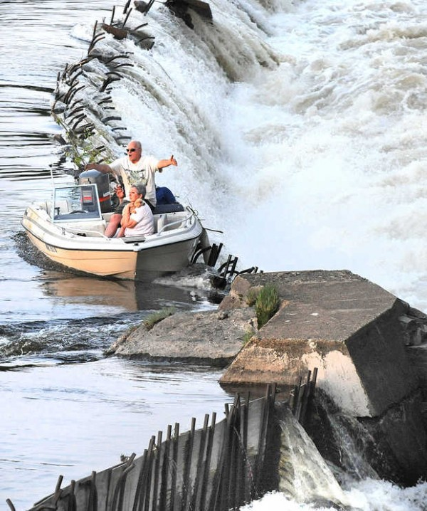 Paul Duclos of Lewiston talks with Auburn firefighters on the shore of the Androscoggin River just above the railroad trestle over the Great Falls on Thursday night after the motor on his boat died and it drifted downriver before getting hung up on the grates of the dam. His wife, Arlene, holds their dog Reese as they await rescue.
