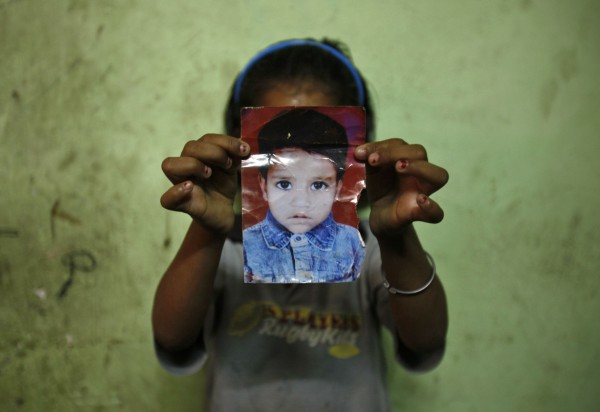 A 7-year-old poses with a photograph of her missing sister inside their home in New Delhi, India.