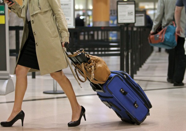 A passenger carries her rolling luggage near the security checkpoint at Hartsfield-Jackson Atlanta International Airport in Atlanta, Ga. From change fees on most discount fares to new luggage charges, airlines have new ways to pry money from passengers.