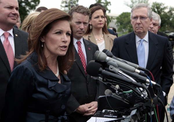 Senate Minority Leader Mitch McConnell listens as Rep. Michele Bachmann speaks at a press conference with Tea Party leaders on Capitol Hill in Washington May 16, 2013.