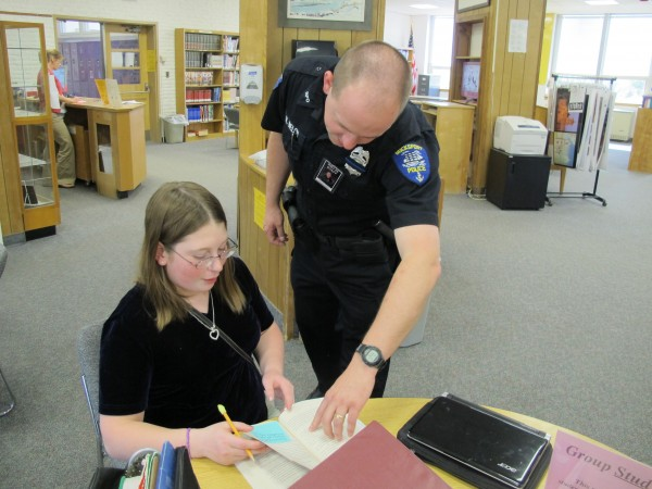 School Resource Officer Ryan Welch leans in to check out a book being read by Bucksport High School freshman Ariel Chase on Wednesday, May 15, 2013.