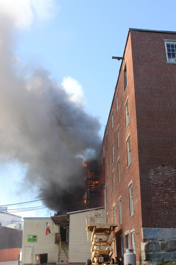 Firefighters work to extinguish a fire at 18 Main St. in Waterville on Friday afternoon.