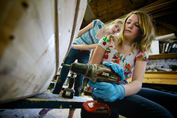 South Bristol eighth-grader Jillian Page, 14, puts a screw into a skiff while classmate Julianna Preston, 13, looks on in the boat shop at the Maine Maritime Museum in Bath on Friday.