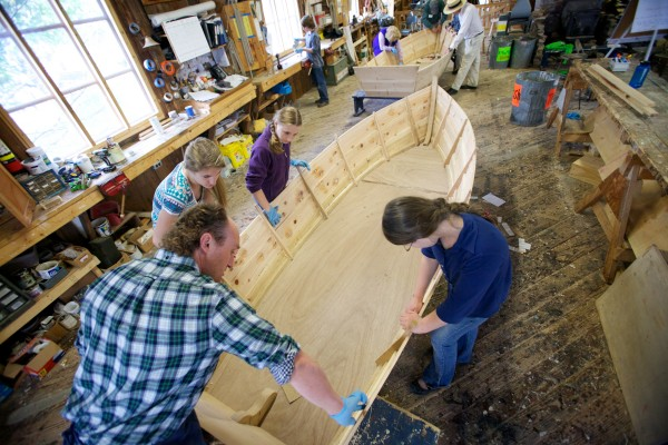 Maine Maritime Museum boat shop manager Kurt Spiridakis works with South Bristol School eighth-graders as they build cedar and oak skiffs Friday in Bath.