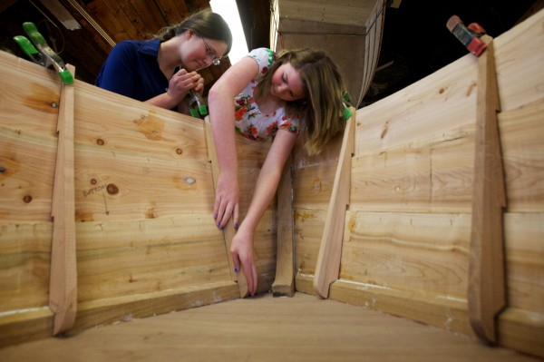 Thalia Eddyblouin, 13, (left) and Jillian Page, 14, clamp pieces into place inside a cedar and oak skiff they're making with classmates from the South Bristol School at the Maine Maritime Museum in Bath on Friday.