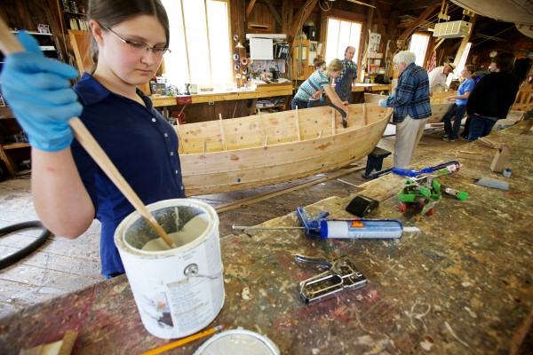 Thalia Eddyblouin, 13, stirs a can of paint in the Maine Maritime Museum's boat shop in Bath on Friday.