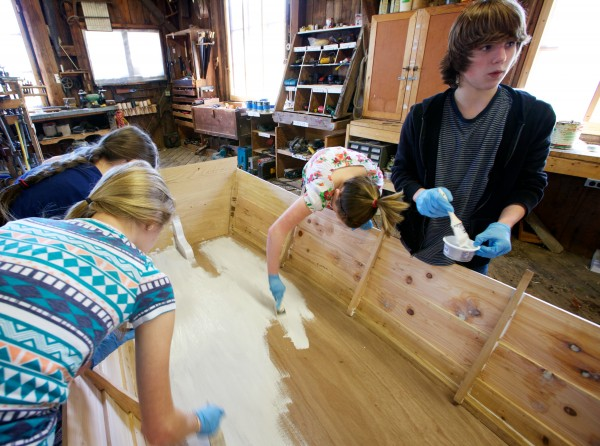 Tyler Giles, 14, the only boy in his five-person eighth-grade class at South Bristol School, paints a cedar and oak skiff at the Maine Maritime Museum in Bath on Friday.